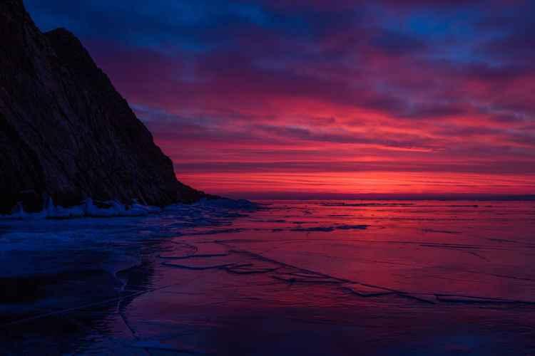 Red dawn on frozen lake Baikal